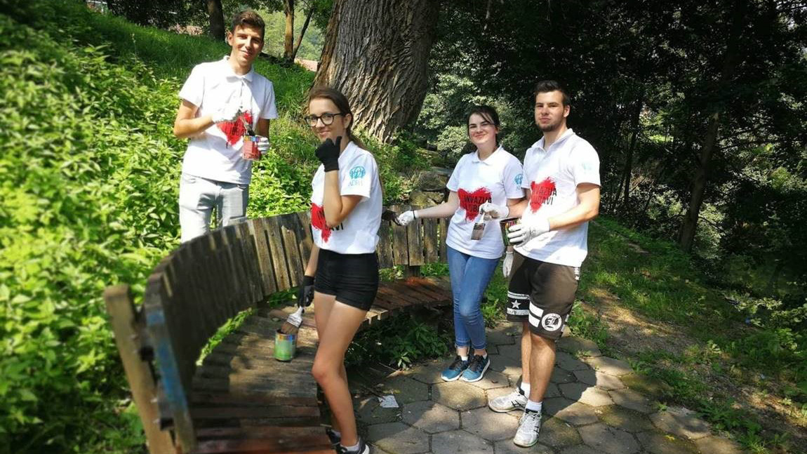 invasion of love volunteers paint a park bench.